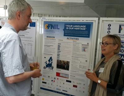Sabine Kirchmeier next to the poster